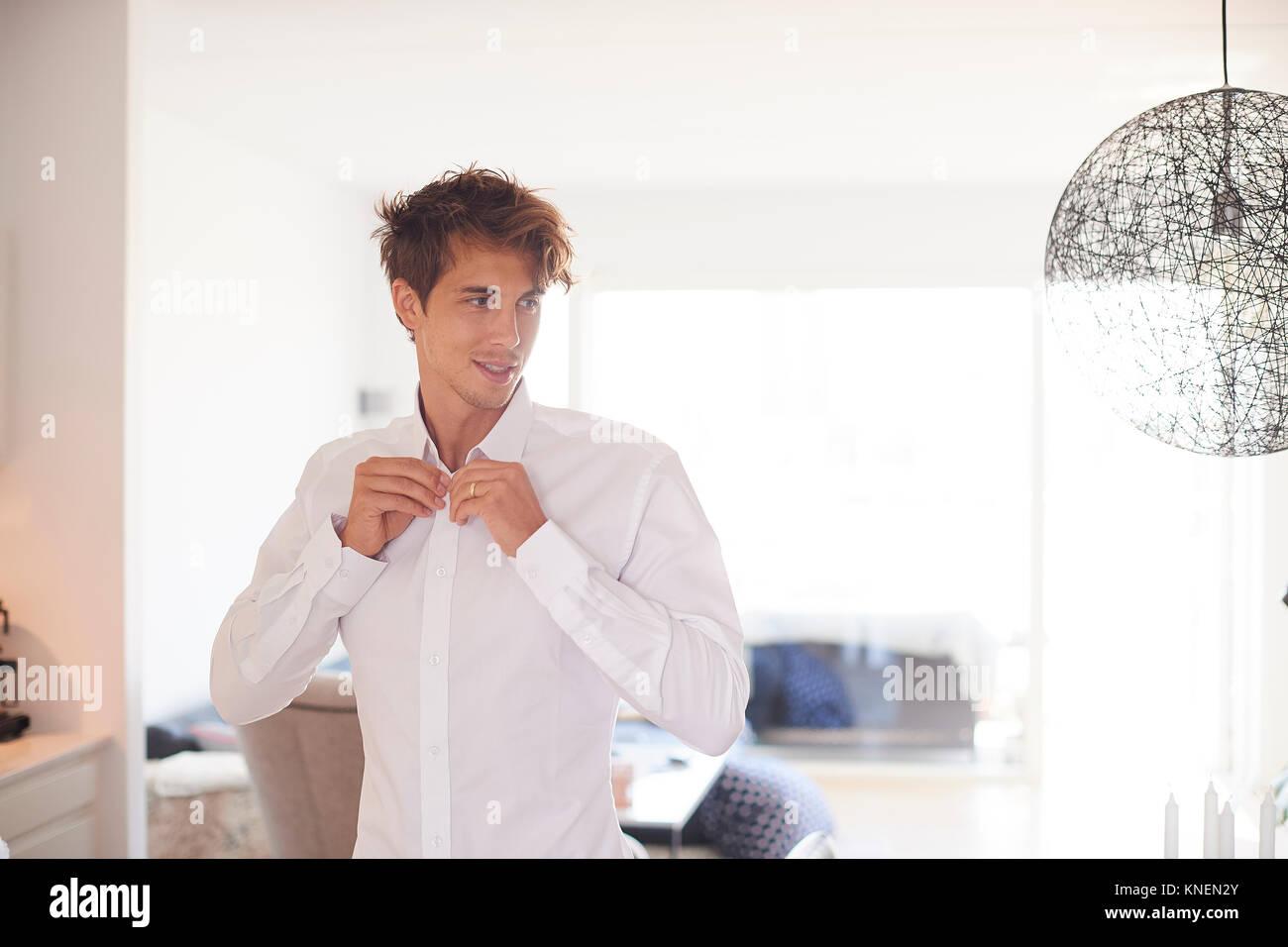 Mitad hombre adulto en el salón para abotonarse la camisa Foto de stock