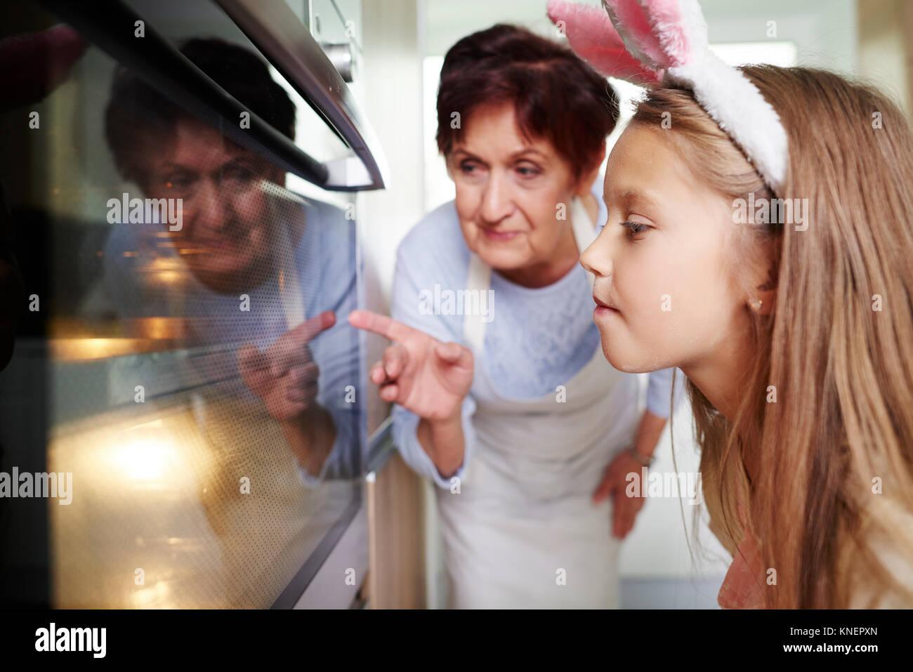 Niña y abuela viendo galletas de pascua en Cocina Microondas Imagen De Stock