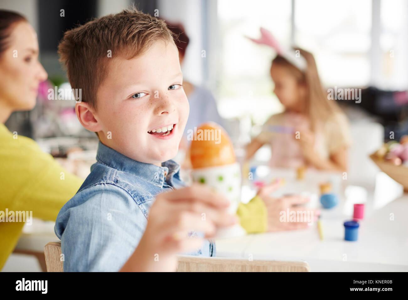 Retrato de niño sosteniendo hervidos pintados del huevo de pascua en la mesa Foto de stock