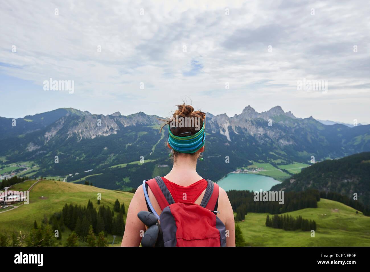Vista trasera del excursionista hembra mirando a lo largo de valle en las montañas Tannheim, Tirol, Austria Imagen De Stock