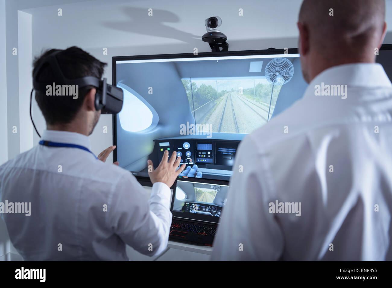 El instructor y el aprendiz mediante sistema de Realidad Virtual en instalaciones de ingeniería ferroviaria Imagen De Stock