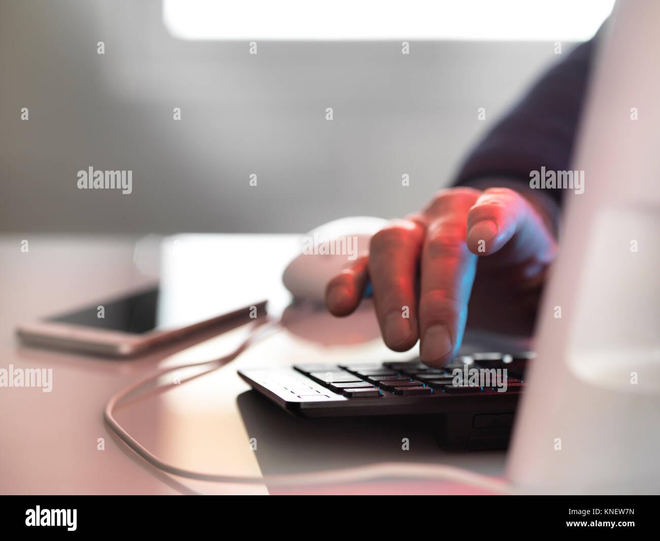 Hacker en el ordenador portátil con teléfono móvil Foto de stock
