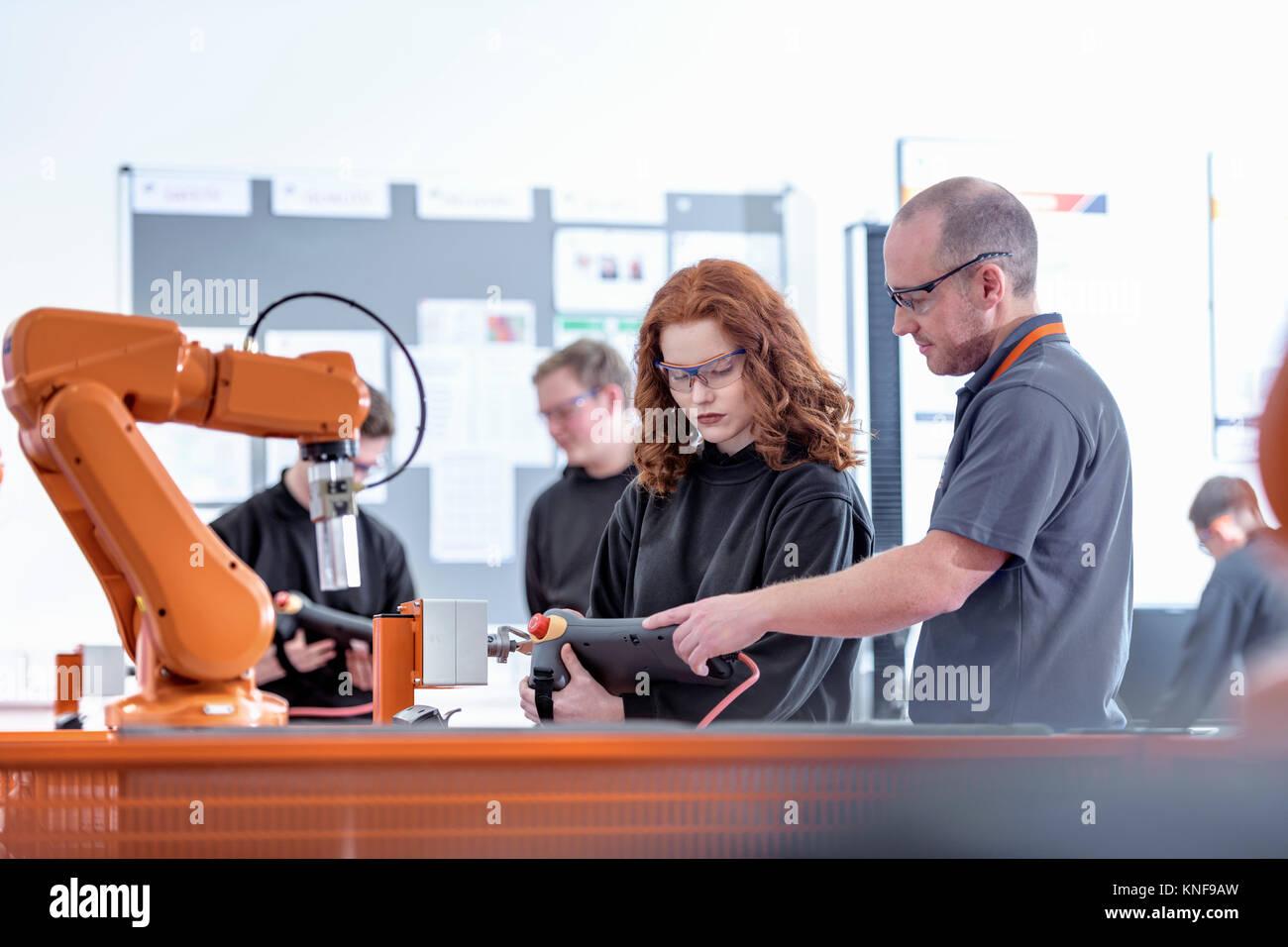 Tutor con robótica aprendices mediante test robots industriales en instalaciones de robótica Imagen De Stock