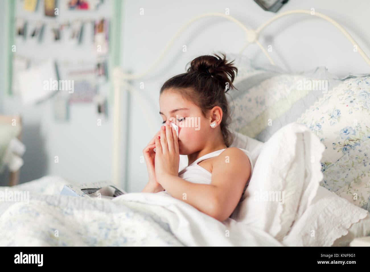 Chica en la cama sonarse la nariz en el pañuelo Foto de stock