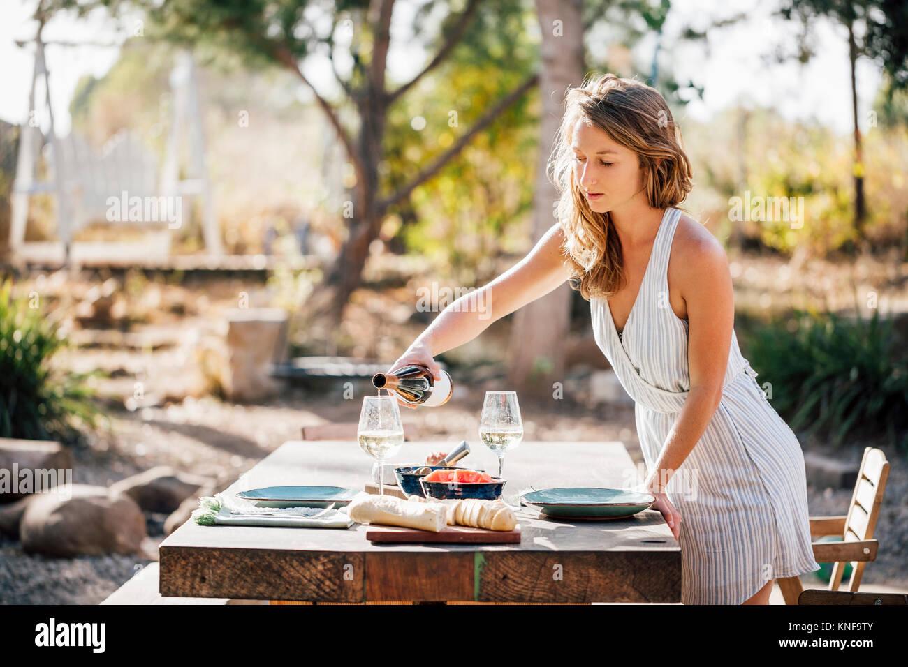 Mujer joven, al aire libre, preparar la mesa, servir vino Imagen De Stock