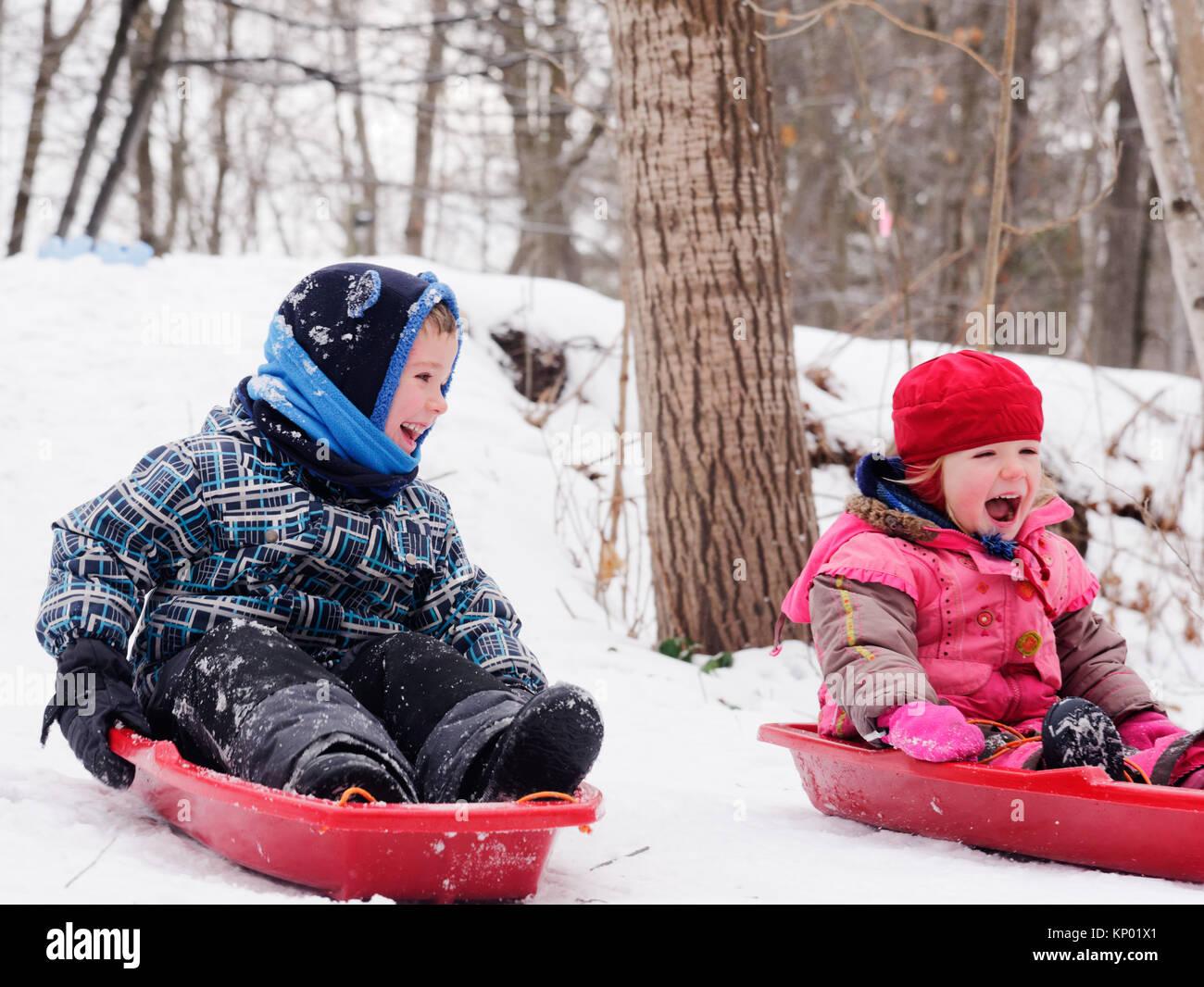 Hermanos y hermanas (5 y 3 años) trineo juntos en Quebec en invierno Imagen De Stock