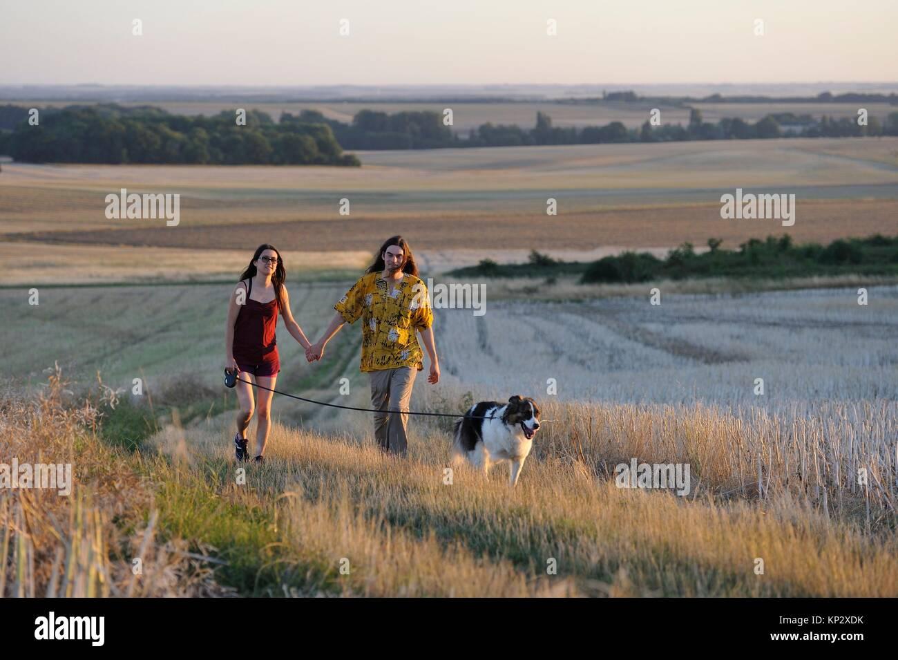 Par de jóvenes caminando con un perro alrededor Mittainville, departamento de Yvelines, la región Ile-de-France, Francia, Europa. Foto de stock