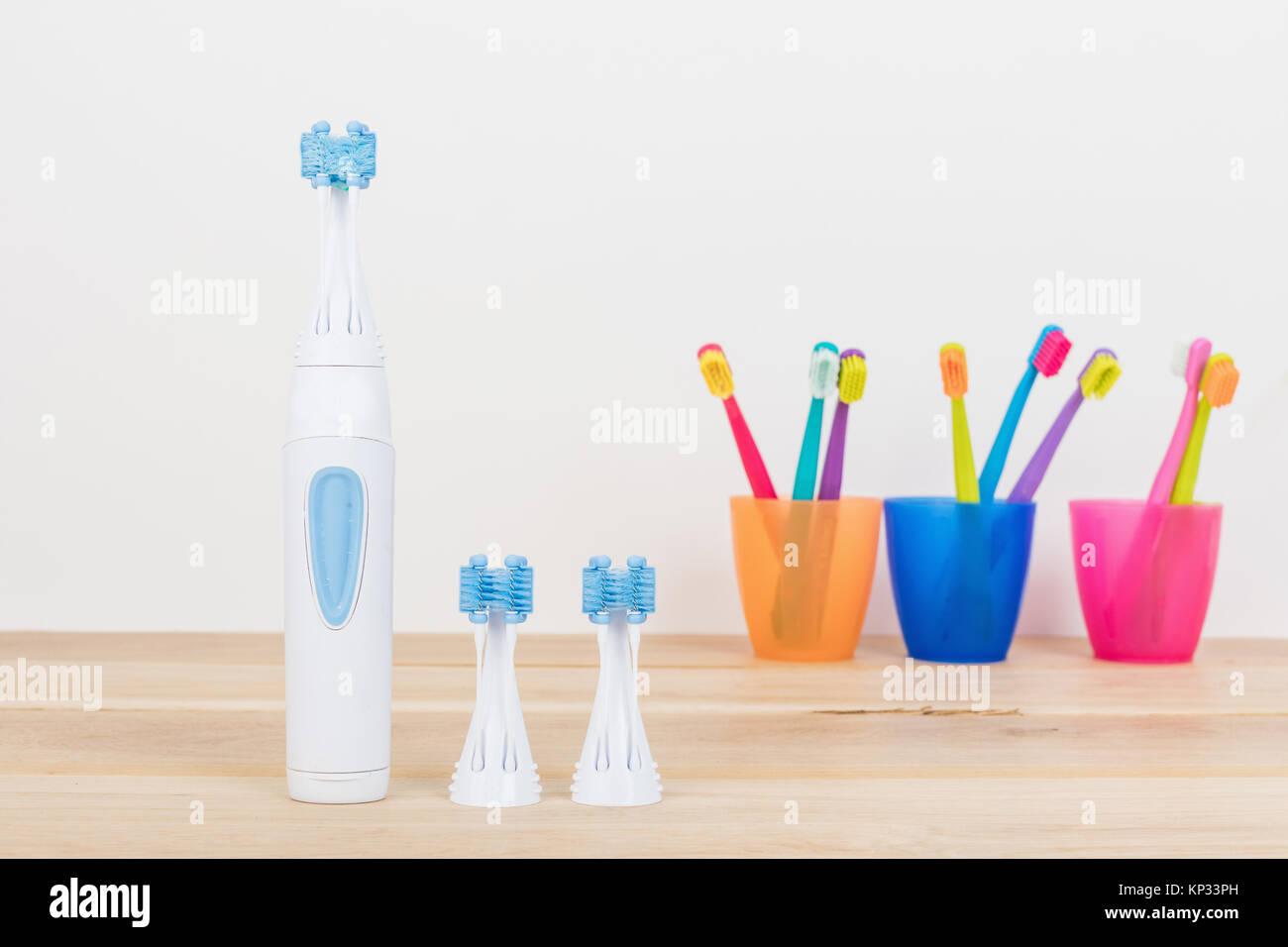 Cepillos de dientes ultra fina en coloridos vasos y cepillo de dientes  moderno eléctrico closeup. 3bf579ab1c4a