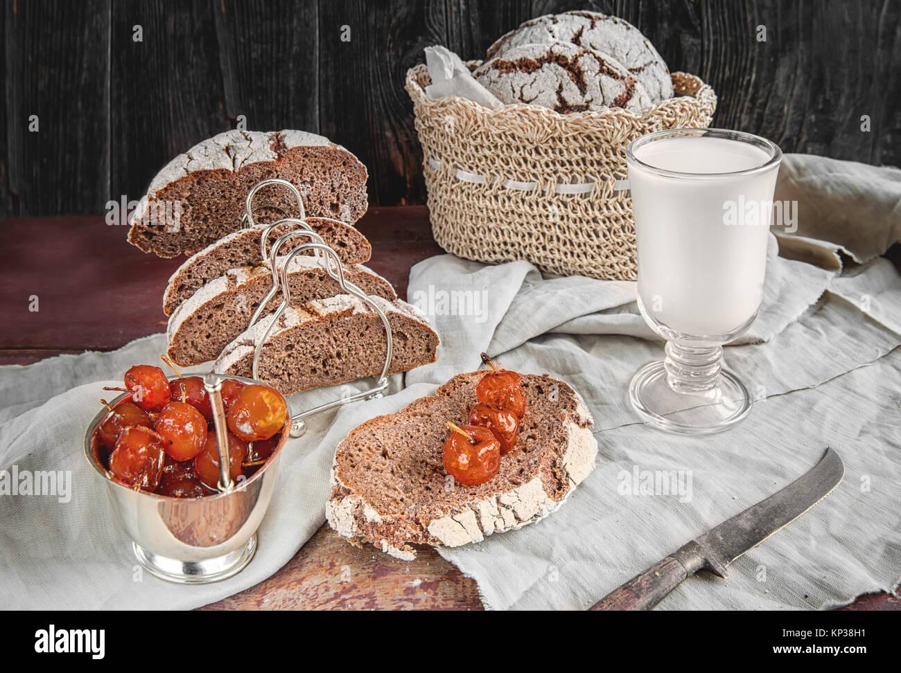 Hermosa hogaza de pan de trigo blanco en una placa en un borde de lino. Repostería casera con mermelada de Imagen De Stock