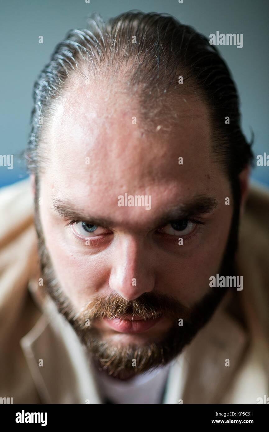 Tilburg, Holanda. Studio retrato adulto joven hombre enojado con emociones y miradas amenazantes. Imagen De Stock