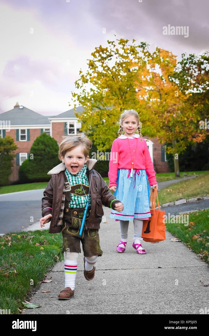 Adorable hermano y hermana hermanos caminando calle abajo para ir con la tradición del truco o trato de Halloween Imagen De Stock