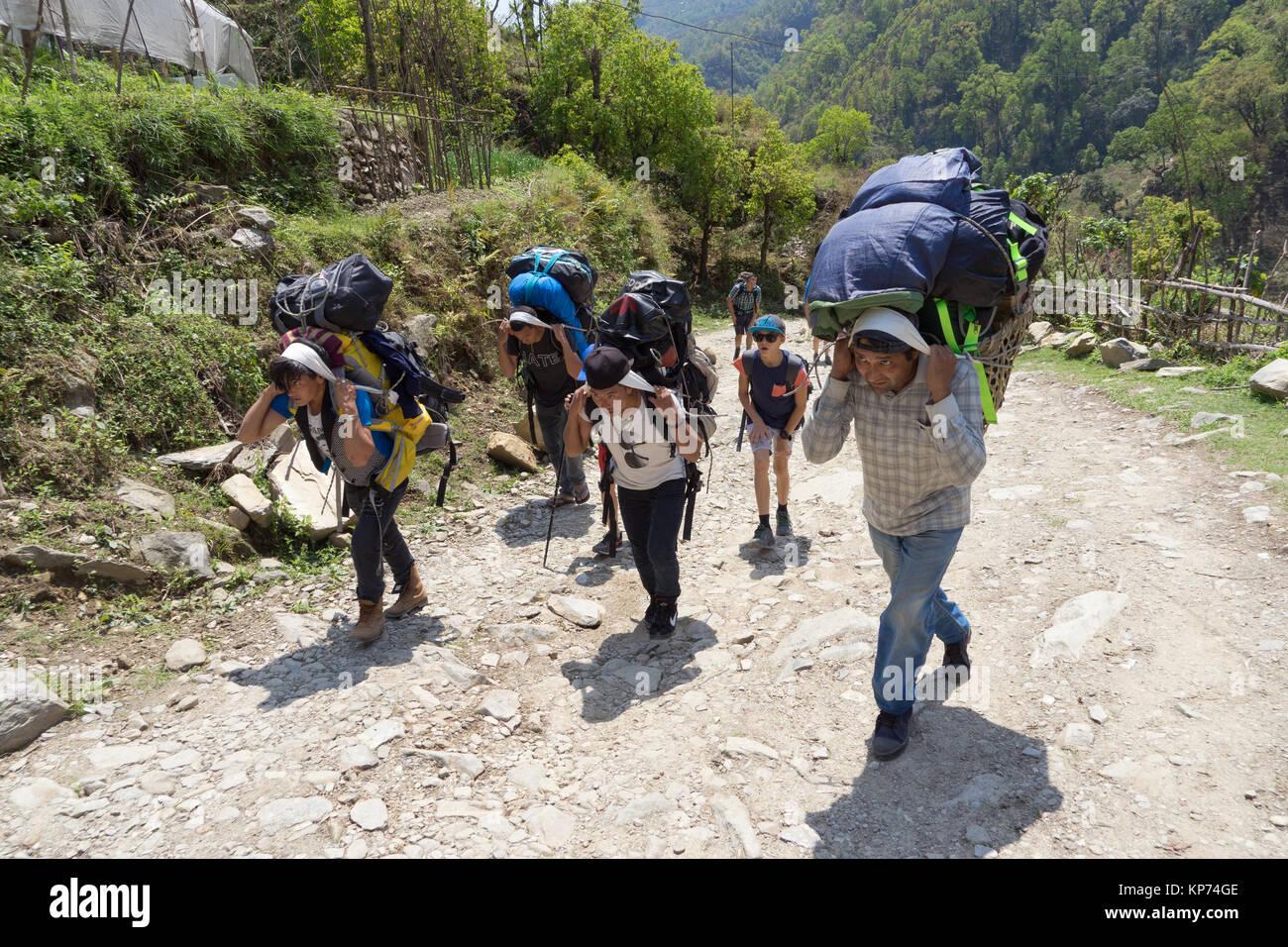 Cargadores de Nepal trekker bolsas de transporte cuesta arriba en el santuario de Annapurna trek. Imagen De Stock