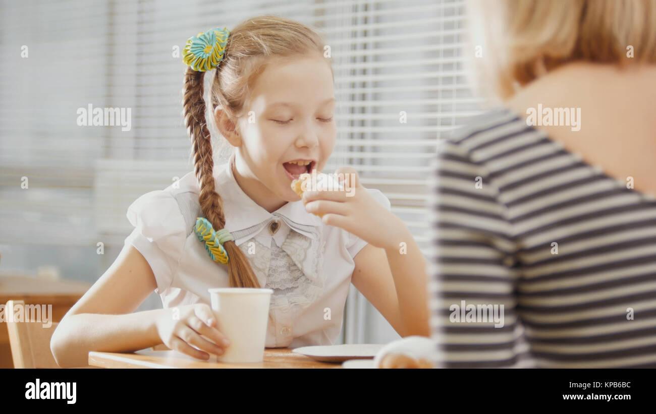 Chica con pigtails come pasteles con su madre en la cafetería Imagen De Stock