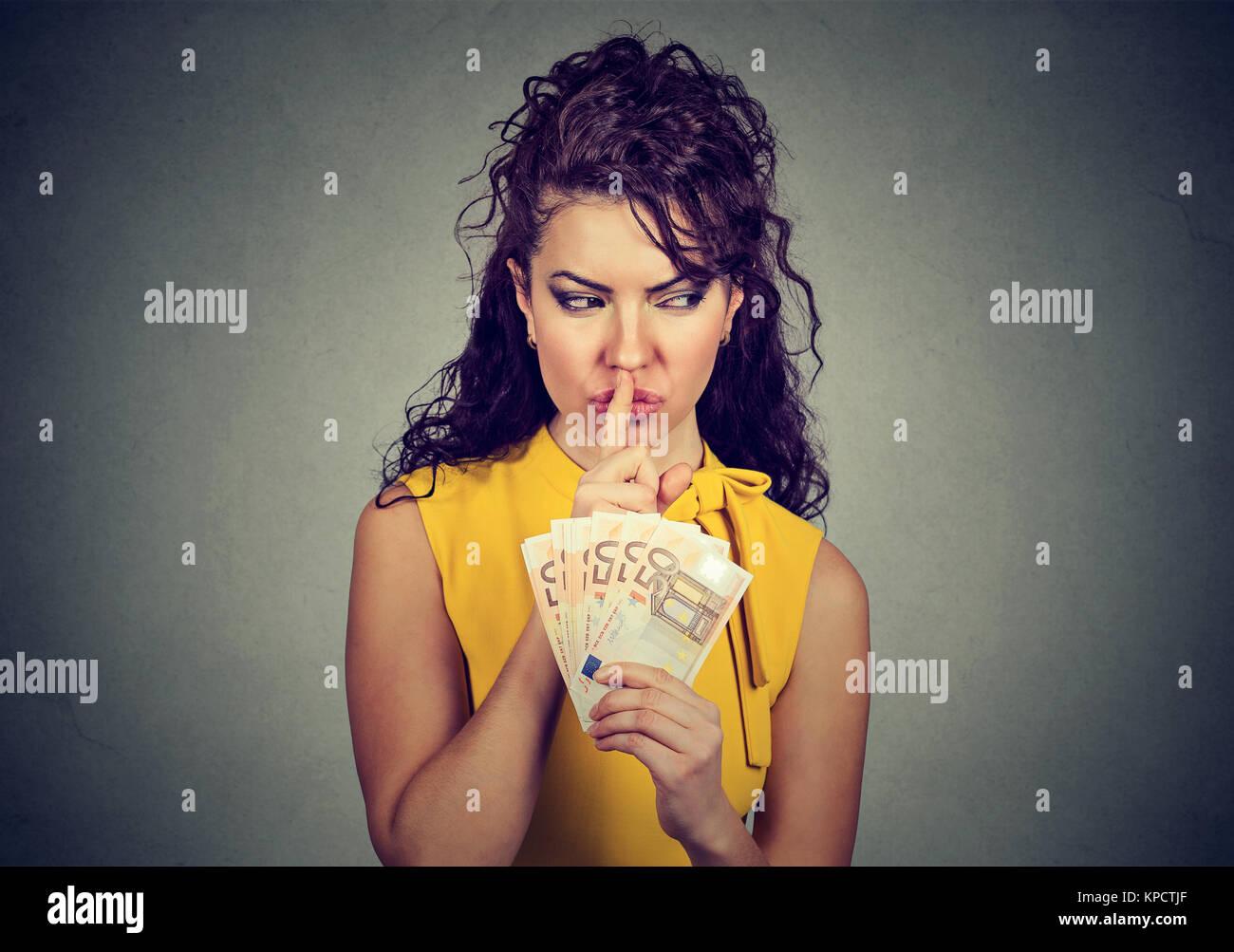 Mujer sosteniendo montón de euros y pidiendo silencio mientras practican la corrupción. Imagen De Stock