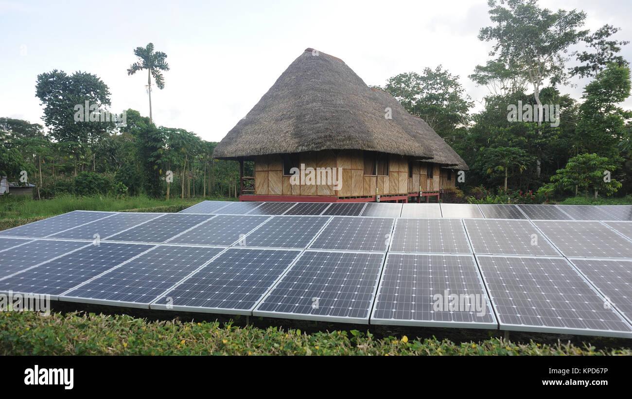 Los paneles solares generan electricidad fuera de una tradicional casa de techo de hojas de palmera en la comunidad Imagen De Stock