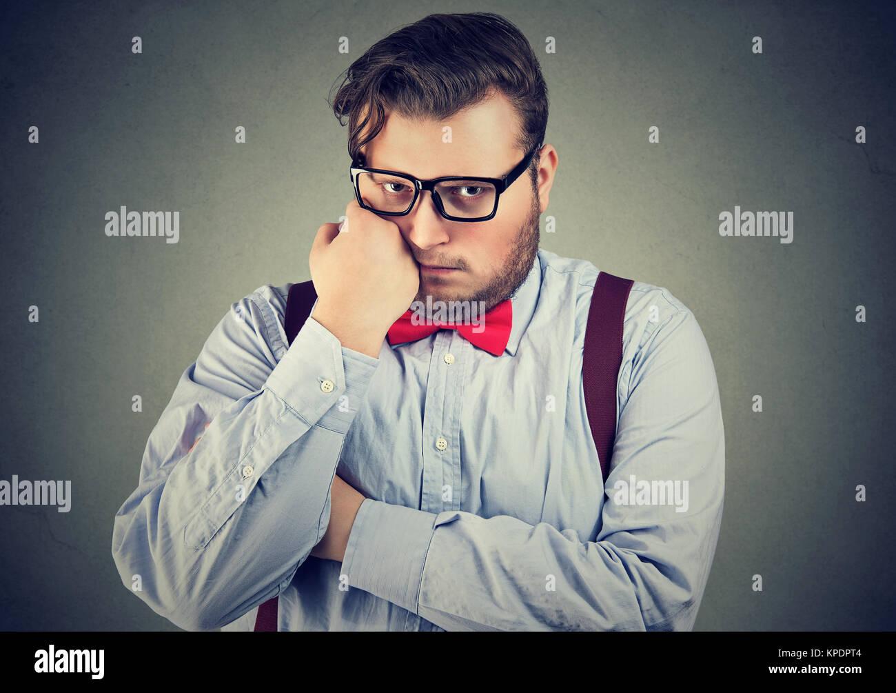 Joven hombre gordito en ropa formal buscando celoso y solitaria mirando a la cámara. Imagen De Stock