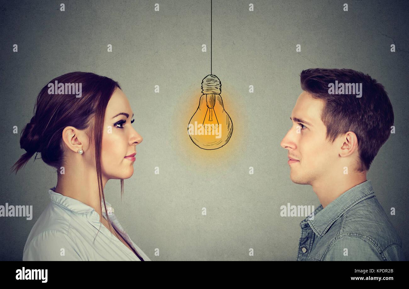 Habilidades cognitivas capacidad concepto, hombres vs mujeres. Hombre y mujer mirando Brillante Bombilla Luz Imagen De Stock