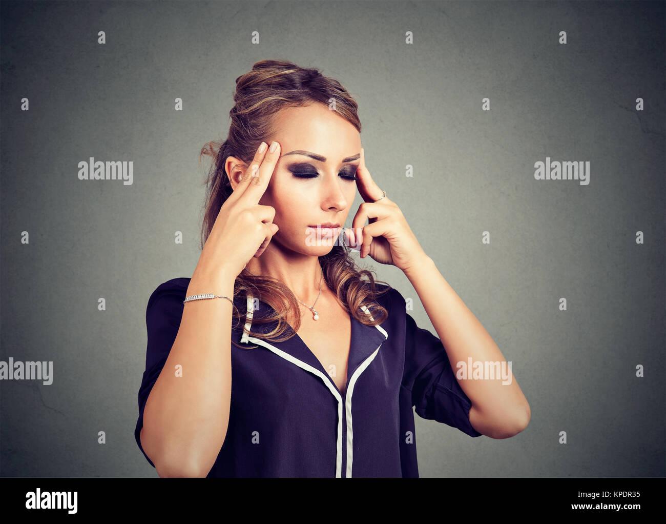 Joven Mujer concentrada rozando los templos buscando agotado y abrumado. Imagen De Stock
