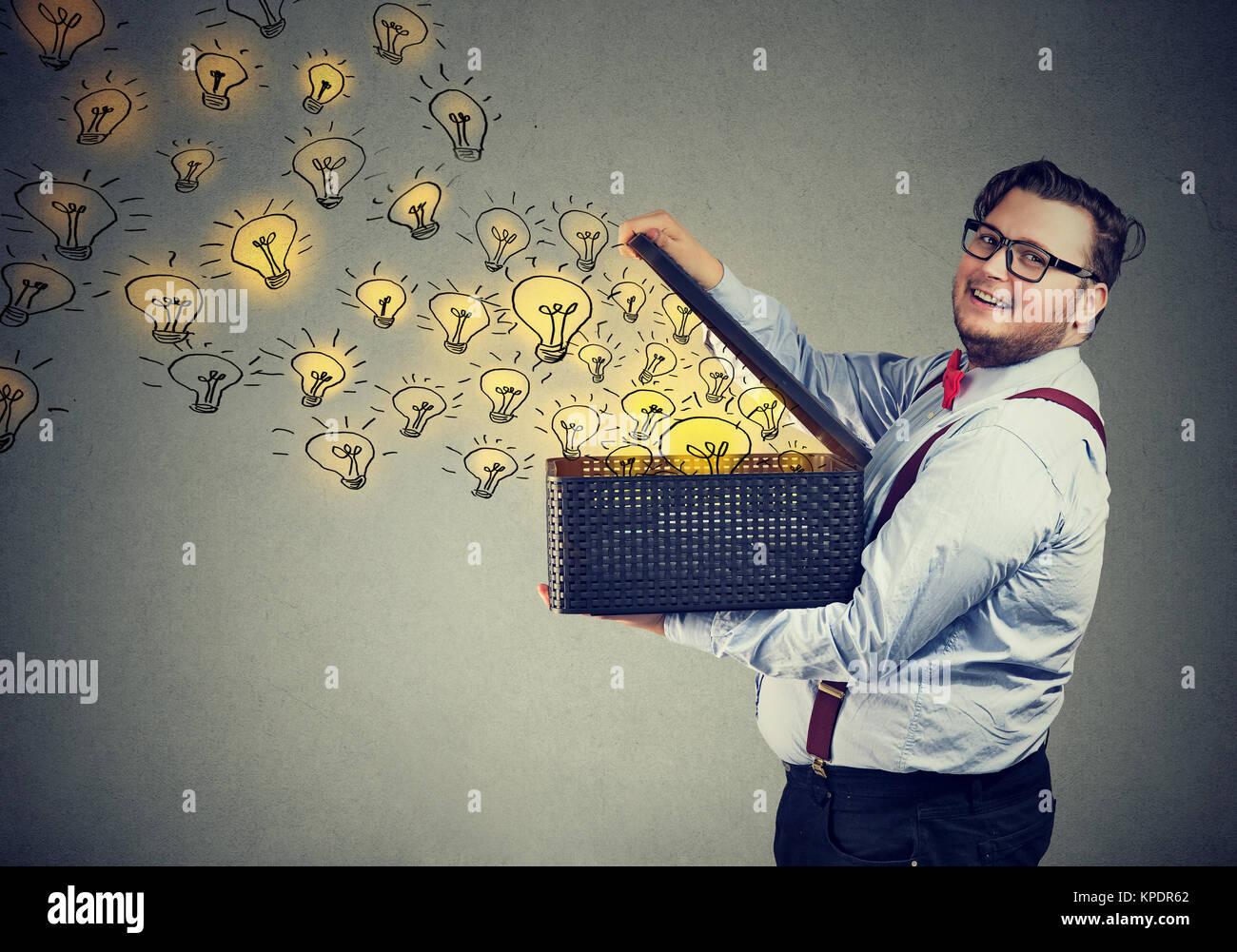 Vista lateral del robusto hombre sujetando la caja con ideas brillantes bein creativa y sonriendo ante la cámara. Imagen De Stock