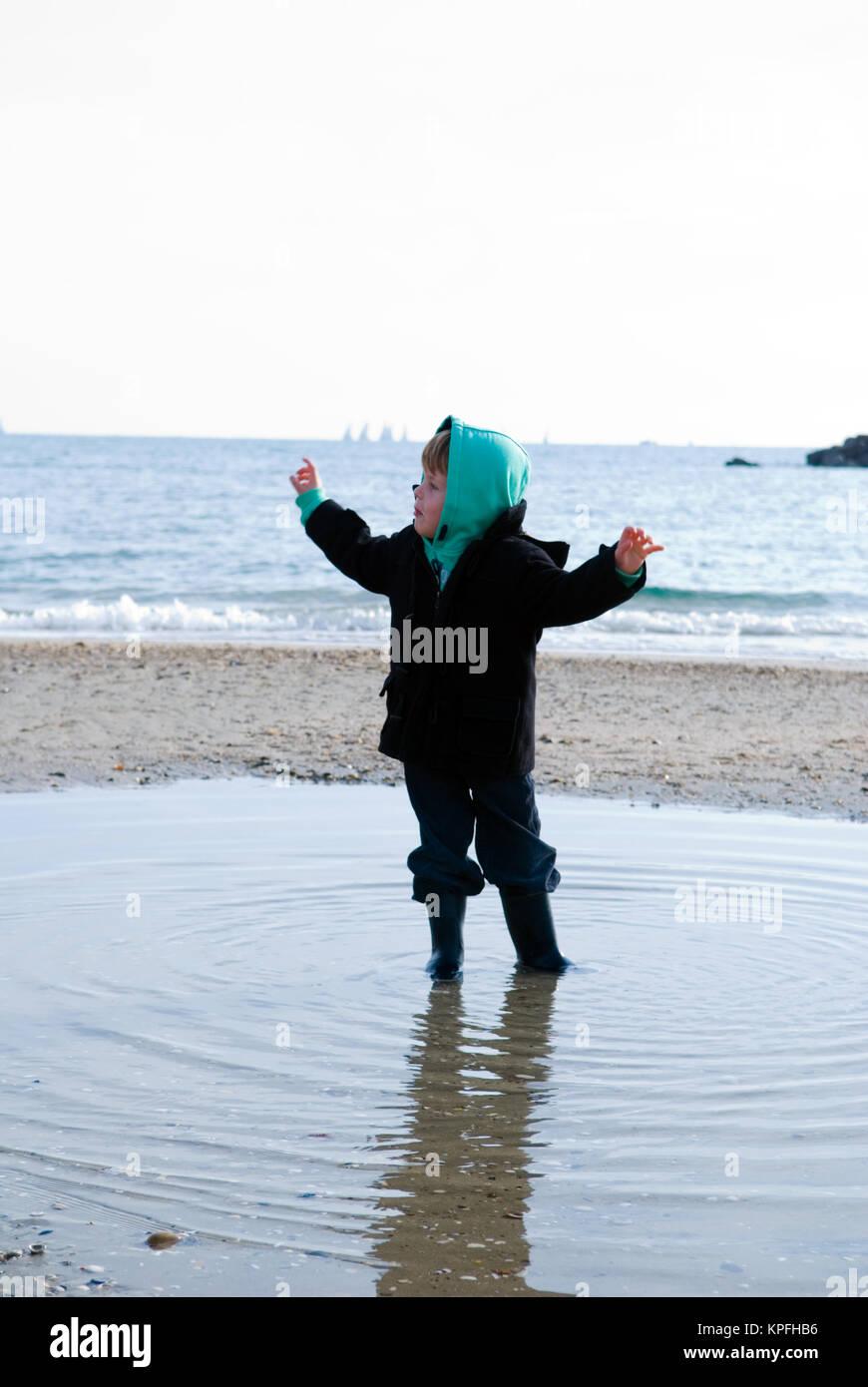 Foto de un niño de cuatro años de pie en medio de una piscina natural en la costa de Francia Imagen De Stock