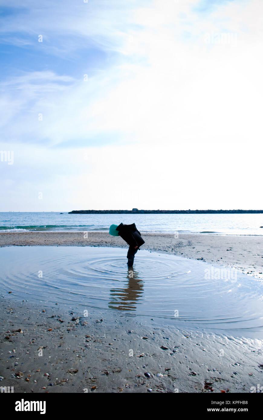 Foto de un niño de cuatro años de pie en medio de una gigantesca piscina y mirando hacia abajo en el agua Imagen De Stock