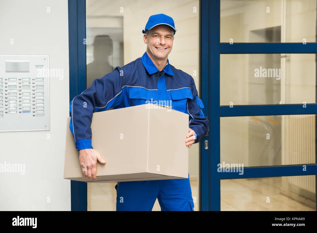 Deliveryman parado cerca del cajón de la puerta Foto de stock