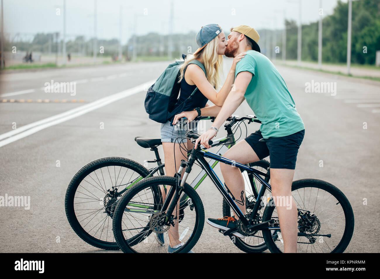 Hermosa pareja joven en amor caminando con bicicletas, besos y abrazos Imagen De Stock
