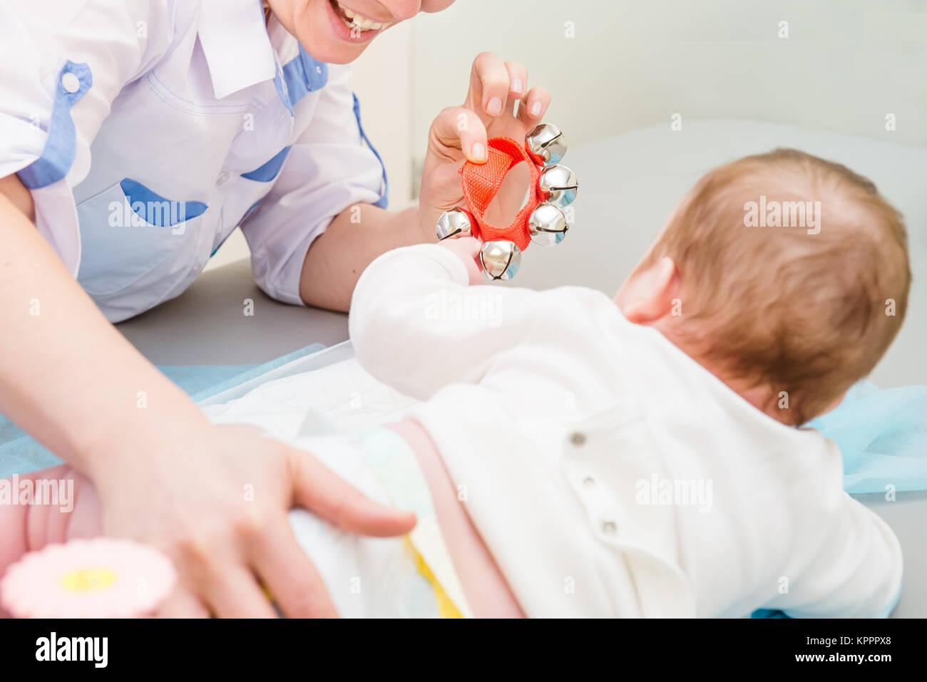Cerrar el doctor con el recién nacido en la moderna clínica pediátrica. Motor infantil educación. El enfoque selectivo. Espacio para el texto Foto de stock