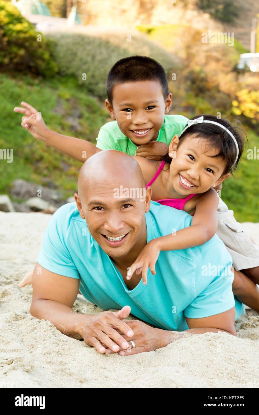 Padre jugando con sus hijos en la playa. Foto de stock