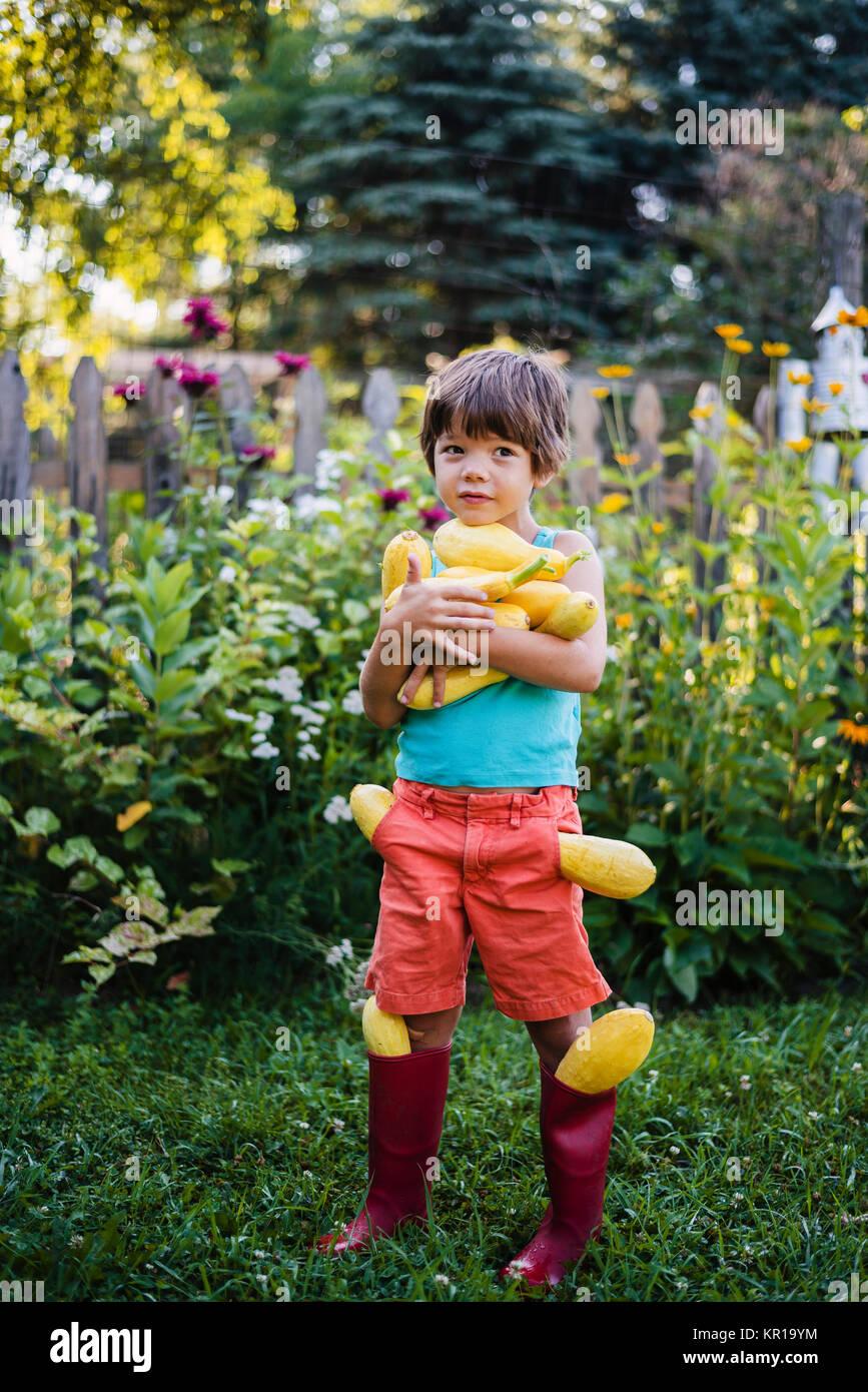 Chico llevando la cosecha fresca de verano de squash Imagen De Stock