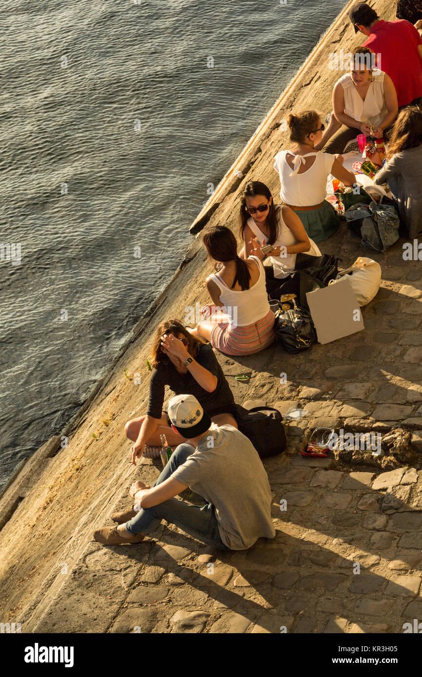 Muchos jóvenes en el verano relajante tarde en île Saint-Louis en las orillas del río Sena en París, Imagen De Stock