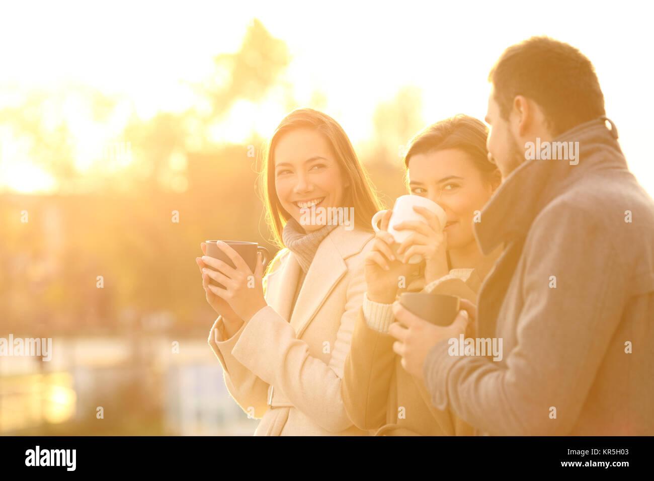 Tres divertidos amigos hablando al aire libre y bebiendo café al atardecer Imagen De Stock
