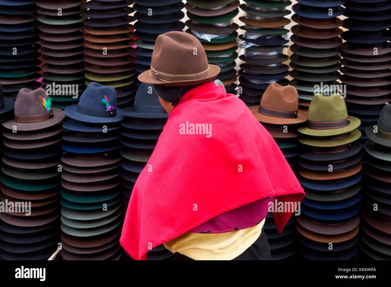 Vista trasera de la mujer vistiendo sombrero marrón y rosa brillante poncho  ecuatoriano tradicional de venta de sombreros de fieltro. 8671ed9b4e1