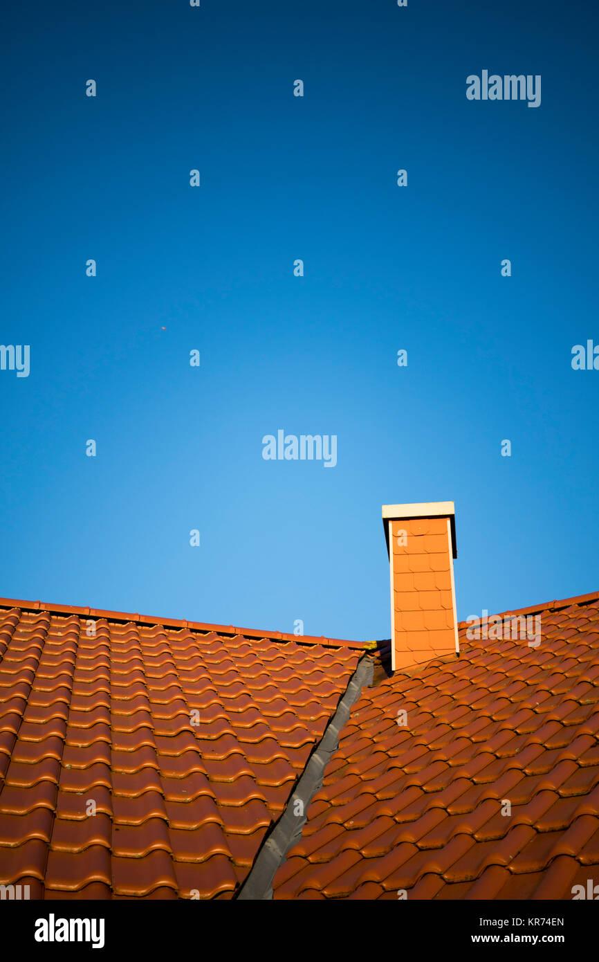 Techo con teja roja y chimenea en la parte delantera de un cielo azul sin nubes Imagen De Stock