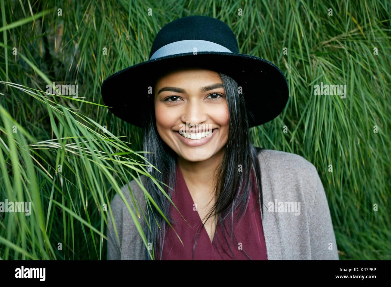 Retrato de mujer de raza mixta sonriente cerca de follaje Foto de stock