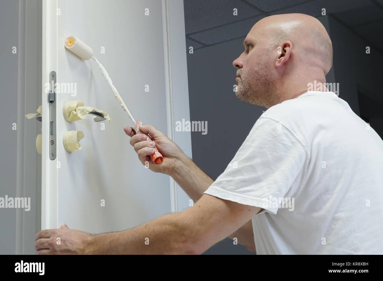 Los artesanos en la pintura de una puerta en un edificio de oficinas Imagen De Stock