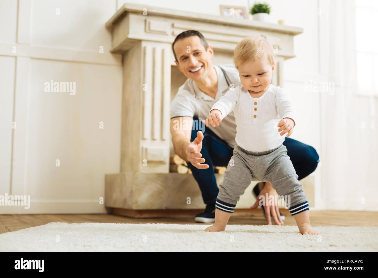 Bebé feliz tratando de estar de pie arriba mientras un alegre padre está listo para ayudar a Imagen De Stock