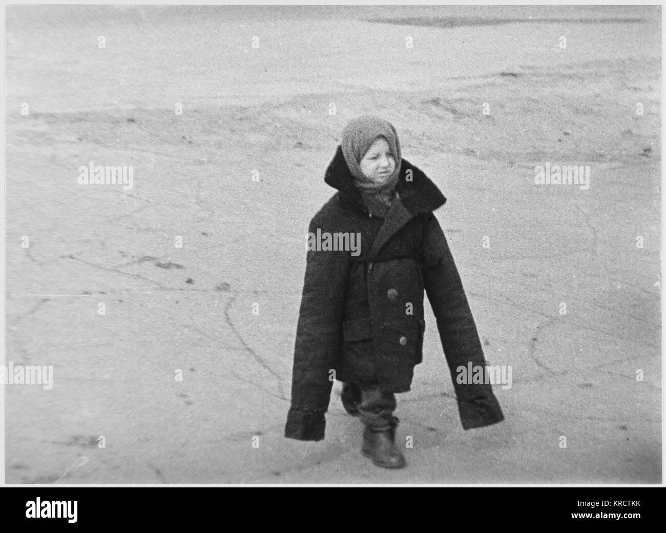 Este huérfano de la guerra soviética ha perdido su hogar y su familia : pero al menos ella se mantiene caliente Foto de stock