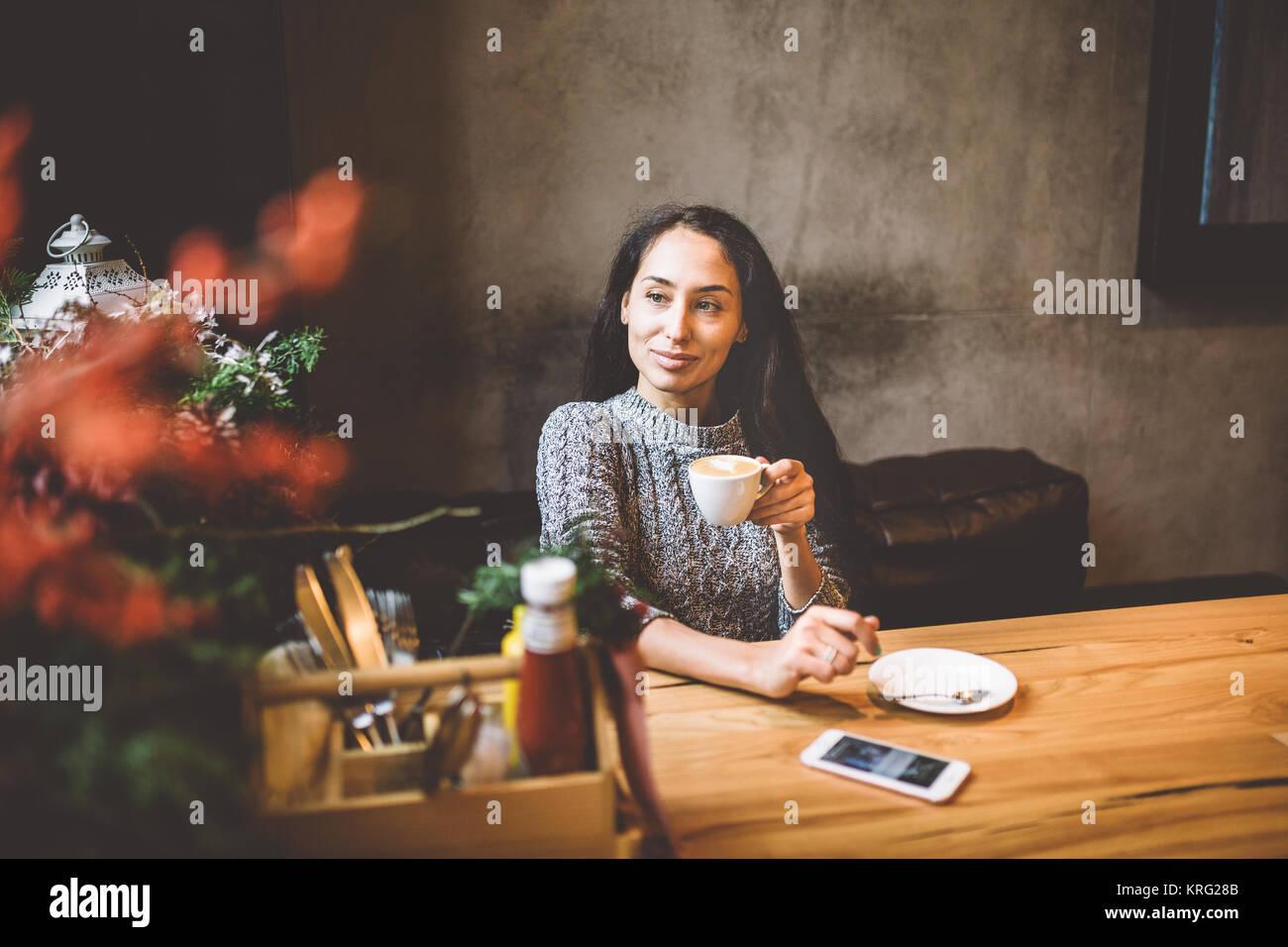 Hermosa niña bebe café en una taza blanca, junto a su teléfono celular en una cafetería decorada Imagen De Stock
