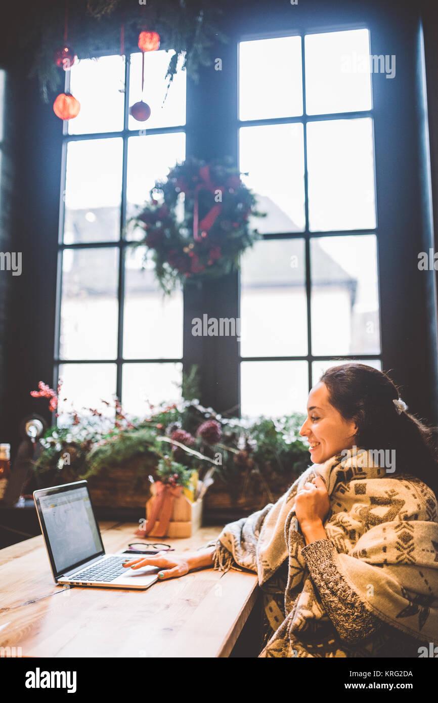 Hermosa joven utiliza la tecnología de ordenadores portátiles, los tipos texto mirando el monitor en una Imagen De Stock