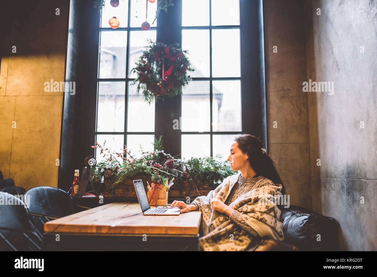 Hermosa joven utiliza la tecnología de ordenadores portátiles, los tipos texto mirando el monitor en una cafetería Foto de stock