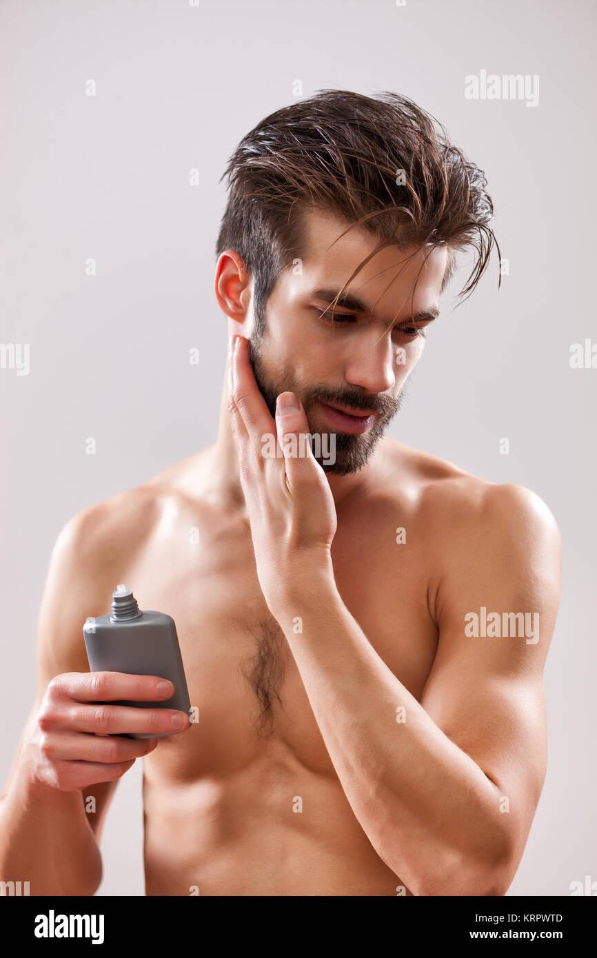 Joven es aplicar lociones para después de afeitar a su cara. Foto de stock