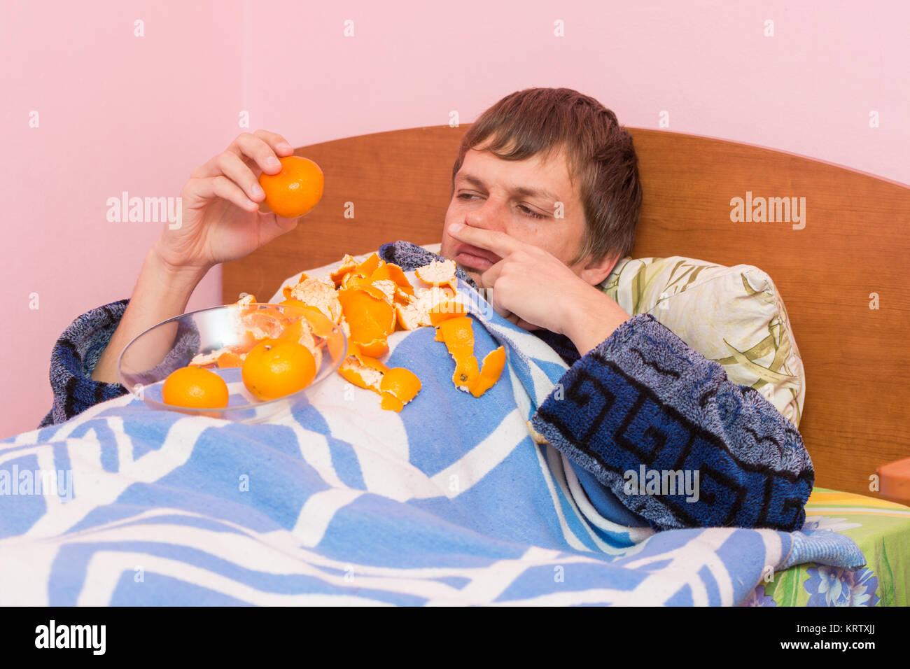 Un hombre que yace en su cama enfermo de mandarinas Imagen De Stock