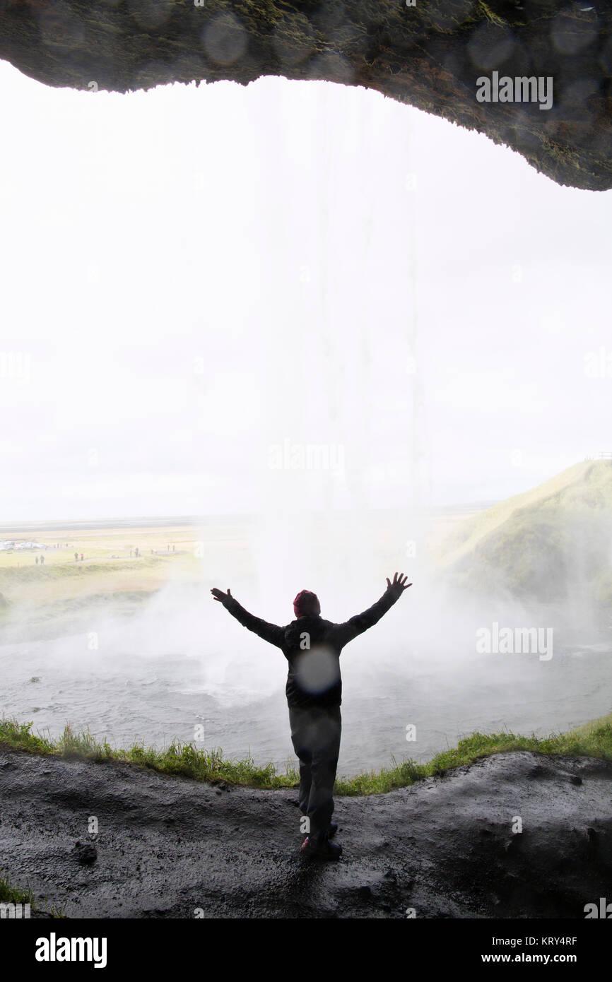 Una mujer de pie con los brazos levantados delante de una cascada. Imagen De Stock