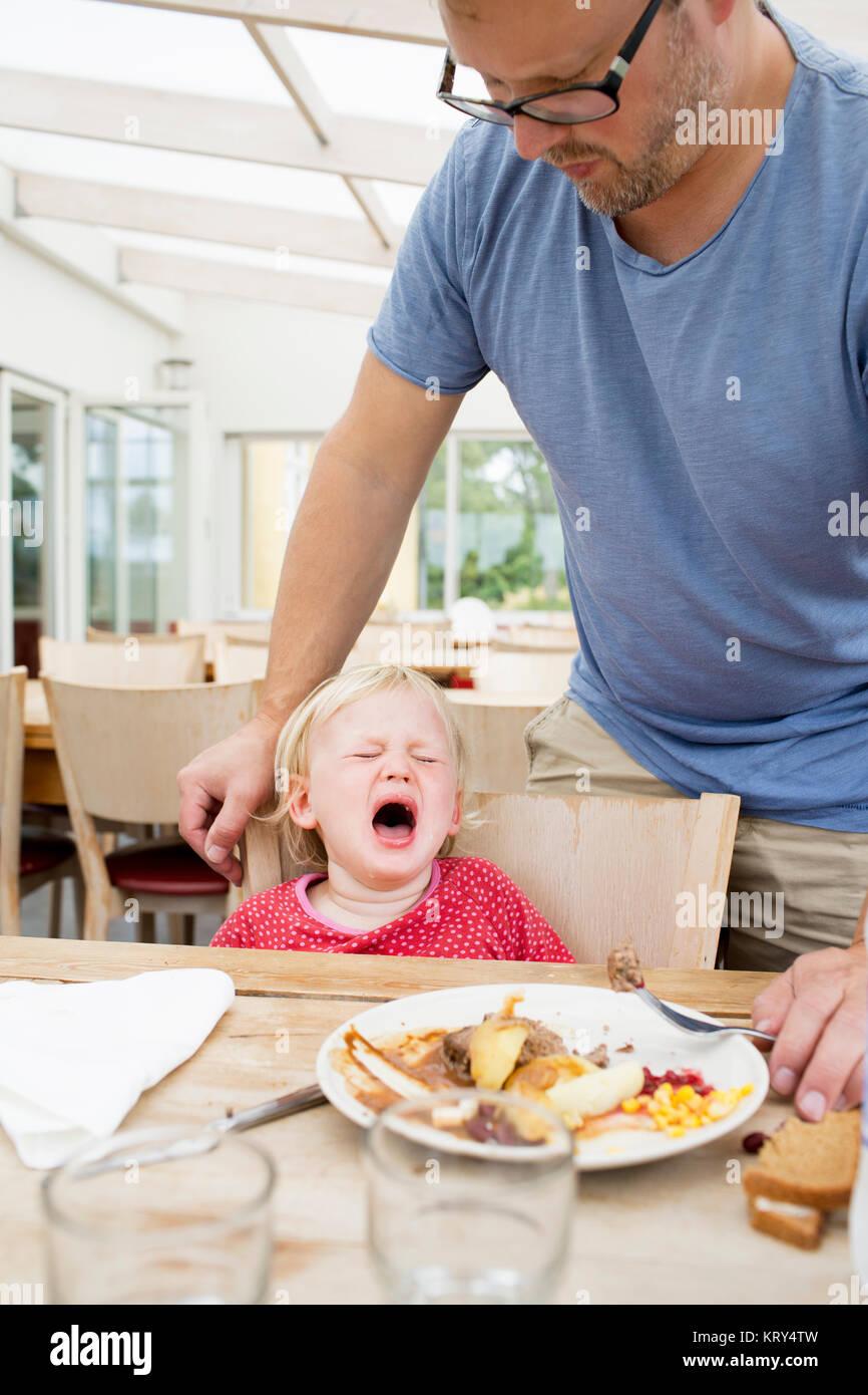 Una chica joven llorando en la mesa Imagen De Stock