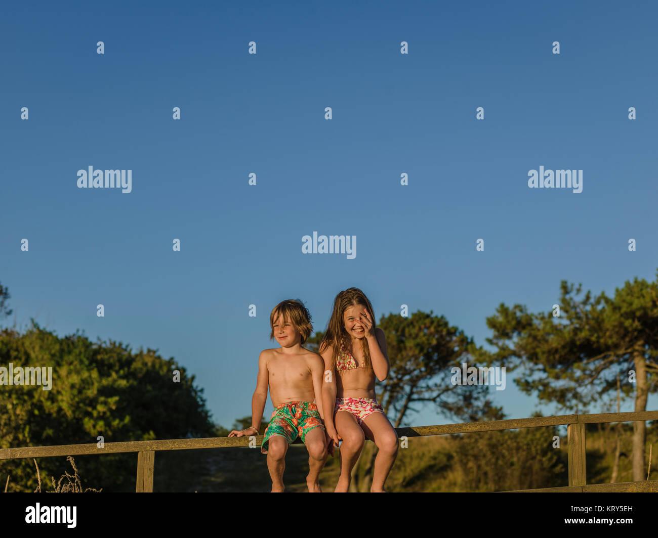 Un chico y una chica sentada sobre un cerco Imagen De Stock