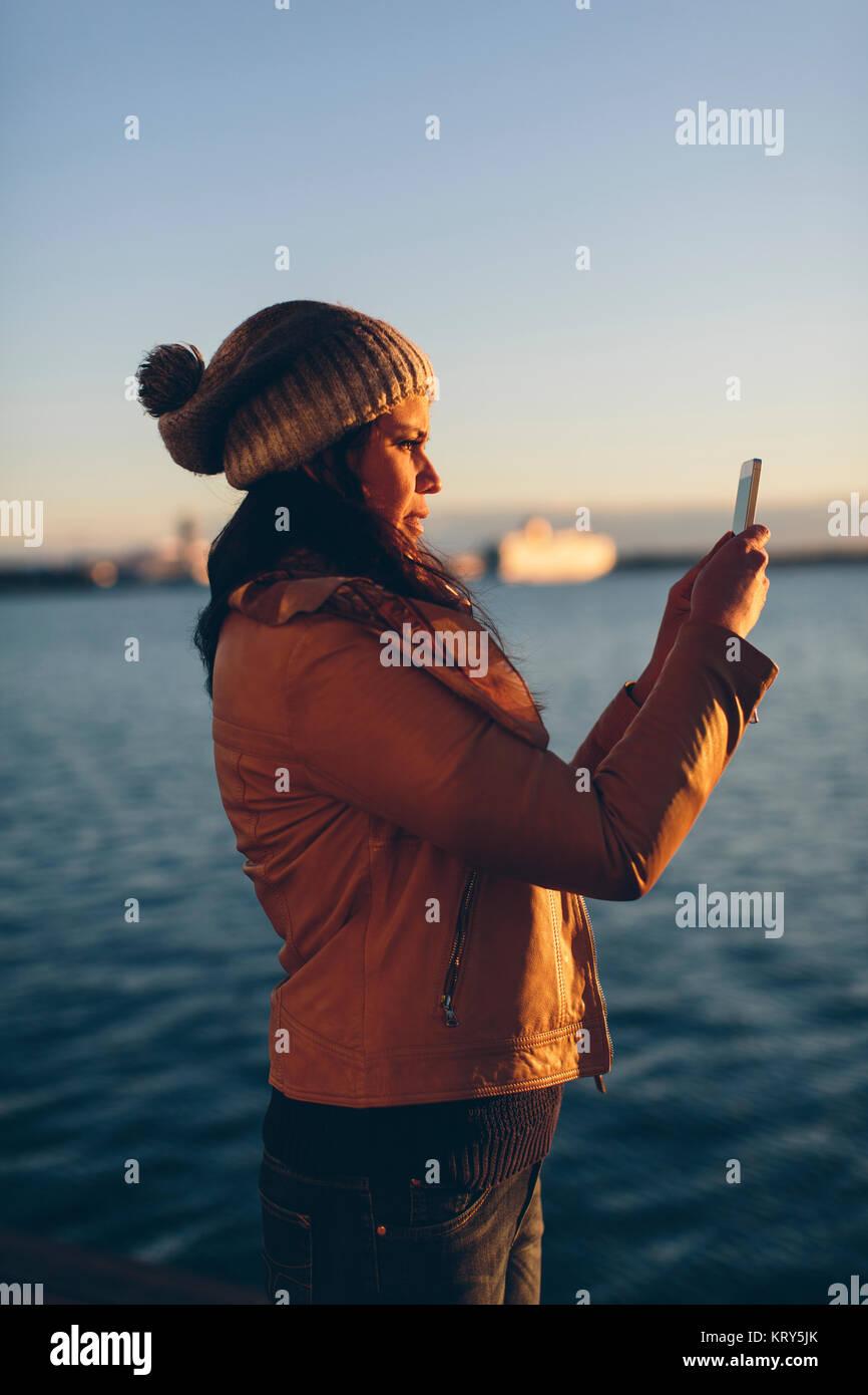 Mujer sosteniendo un teléfono inteligente por el mar Imagen De Stock