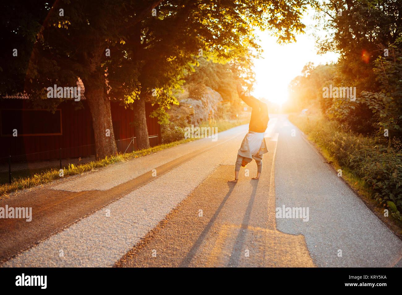 Hombre haciendo el pino sobre una carretera al atardecer en Bohuslan, Suecia Imagen De Stock
