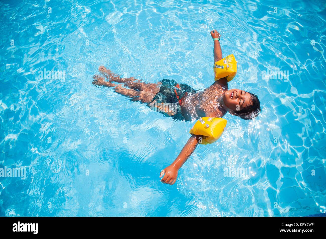 Un niño usando agua alas flotando en una piscina Imagen De Stock
