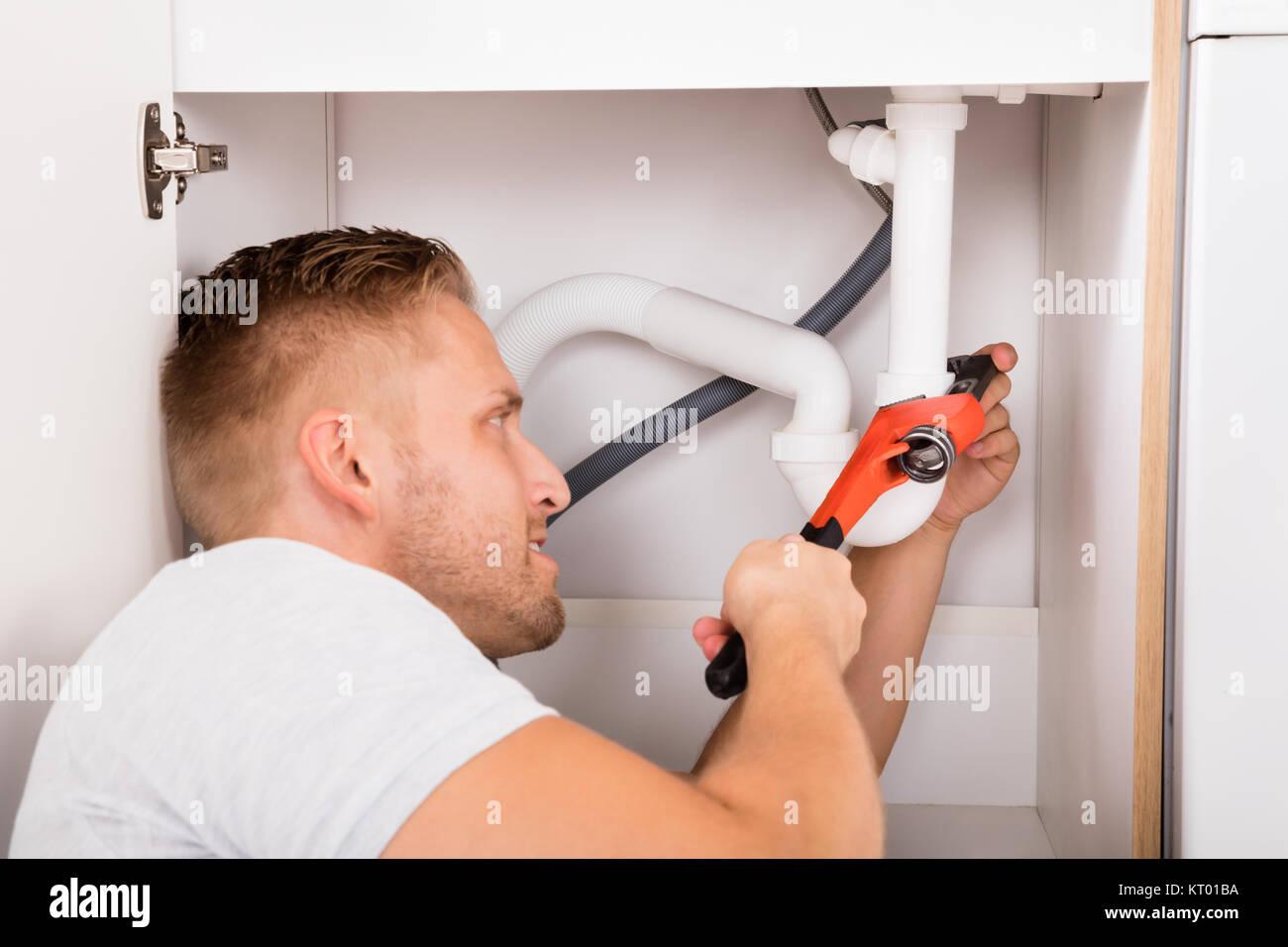 Fontanero masculino Reparación tubo disipador Foto de stock